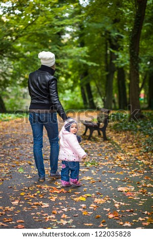 Infant baby girl in golden autumn park