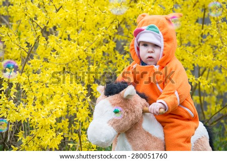 Infant baby girl on horse - stock photo