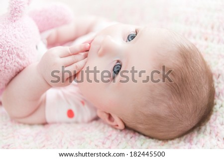 Infant baby girl playing on a pink blanket.