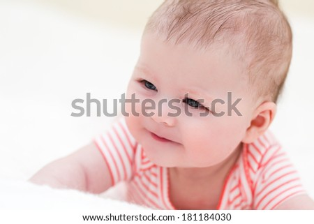Infant baby girl playing on a white blanket.