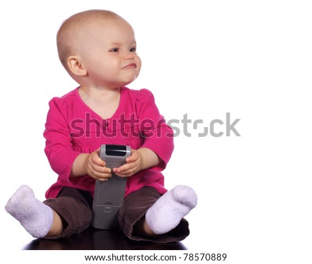 Infant baby girl playing with T.V. remote with a silly smirk on her face