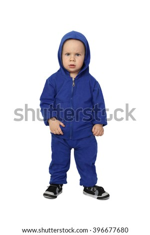 Infant baby in blue suit stands with serious facial expression isolated on white background - stock photo