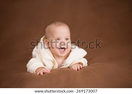 Infant baby in towel on brown background