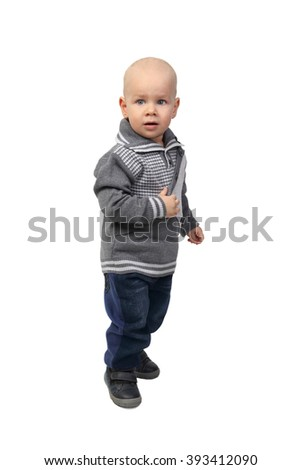 Infant baby in warm clothes standing afraid full height isolated on white background - stock photo