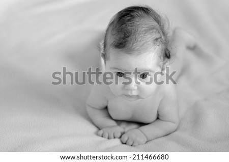 Infant baby lies on tummy in bed. Concept photo of infant baby childhood healthcare development. Copy space (BW) - stock photo