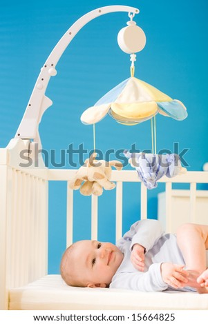 Infant baby resting and playing in his little baby bed at nursery. Toys are officially property released. - stock photo