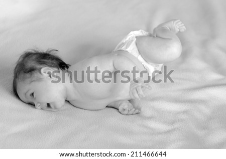 Infant baby roll over in bed.Concept photo of infant baby childhood healthcare development. Copy space (BW) - stock photo