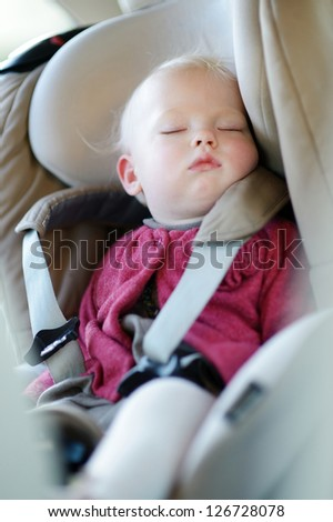 Infant baby sleeping peacefully in a car seat - stock photo