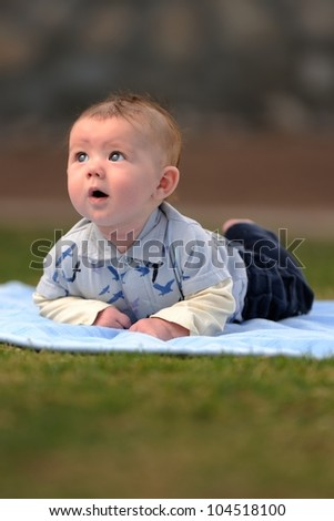 Infant Boy Outside on Blanket Looking Up. Three-month old baby boy outside on a blanket looking up with his face illuminated. Shallow DOF. - stock photo
