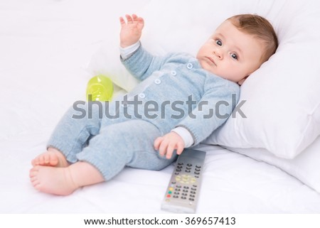 Infant boy with bottle and remote control.
