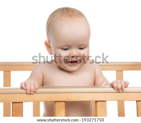 Infant child baby boy in wooden bed looking down on white background - stock photo