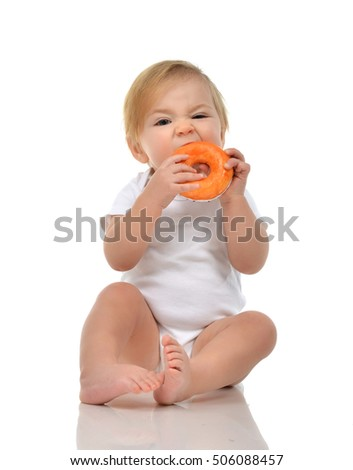 Infant child baby boy toddler eat sweet donut candy fast food isolated a white background