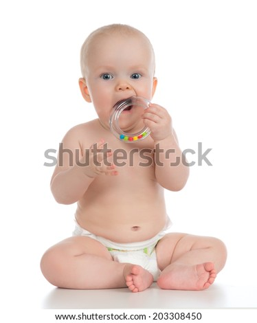 Infant child baby boy toddler playing and eating with circle ring toy in hand  isolated on a white background - stock photo