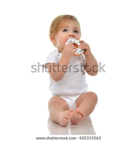 Infant child baby boy toddler playing on a floor with sweet donut fast food isolated a white background