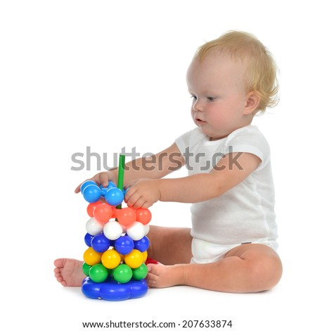Infant child baby boy toddler playing with Pyramid in hand on a floor on and looking up isolated a white background