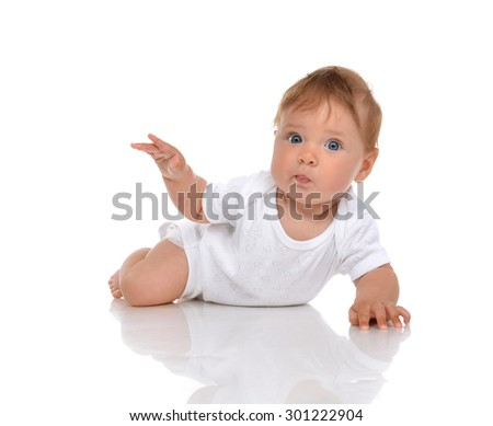 Infant child baby girl lying surprised with hand pointing isolated on a white background - stock photo