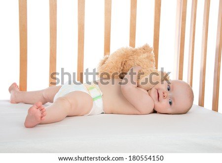 Infant child baby girl toddler lying in bed in diaper hugging teddy bear on white background - stock photo