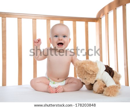 Infant child baby girl toddler shouting or yelling in diaper with teddy bear in a bed on white background - stock photo