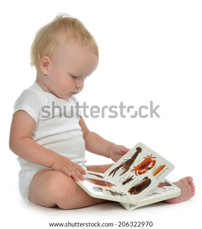 Infant child baby girl toddler sitting and reading book on a white background - stock photo