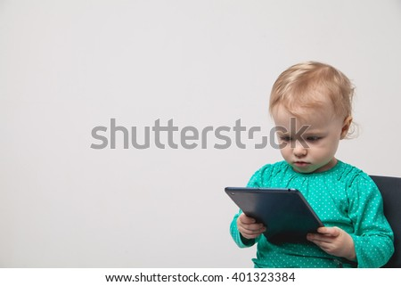 Infant child baby girl toddler sitting and typing digital tablet mobile computer isolated on a white background