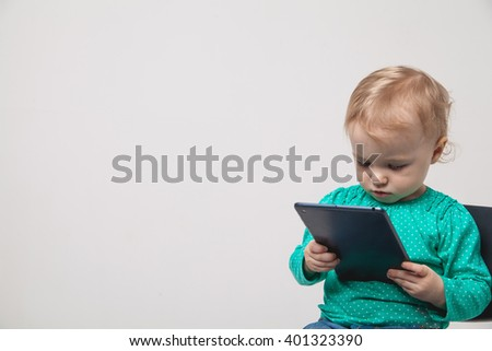 Infant child baby girl toddler sitting and typing digital tablet mobile computer isolated on a white background - stock photo