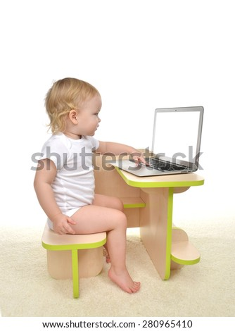 Infant child baby girl toddler sitting with hands typing on modern wireless computer laptop keyboard isolated on a white background - stock photo