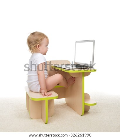 Infant child baby girl toddler sitting with hands typing on modern wireless computer laptop keyboard isolated on a white background