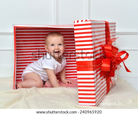 Infant child baby toddler kid sitting in presents gift for celebration. Christmas new year concept.  - stock photo