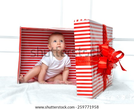 Infant child baby toddler kid sitting in presents gift for celebration for birthday. Christmas new year concept. - stock photo