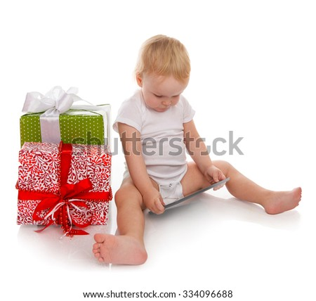 Infant child baby toddler kid with tablet pc device ordering presents gifts isolated on a white background Christmas new year concept. - stock photo