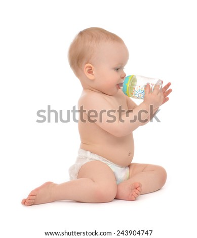 Infant child baby toddler sitting and drinking water from the feeding bottle on a white background