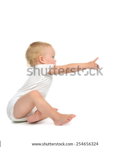 Infant child baby toddler sitting with hand pointing finger straight isolated on a white background - stock photo