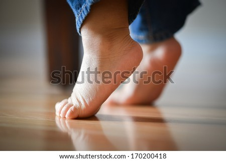 Infant Child's Feet On Tippy Toes - Innocence Concept - stock photo