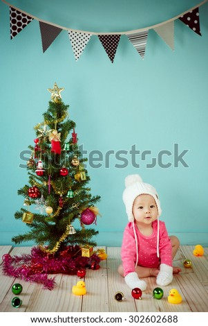 Infant child with white poodle hat and knitted mittens and Decorating Christmas tree on green background - stock photo