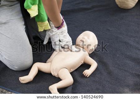 Infant dummy cardiac massage - stock photo