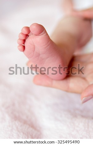 Infant foot on mothers palm