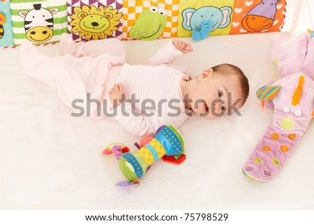Infant girl lying on back surrounded with colorful baby toys? - stock photo