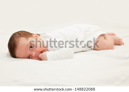Infant laying on his tummy sucking his hand. Selective focus on the eyes - stock photo