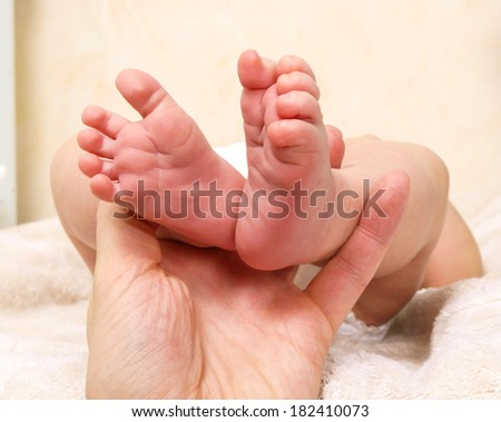 Infant laying on its back with feet held by parent