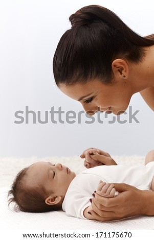 Infant lying on back, mother smiling happy leaning over baby, looking close.