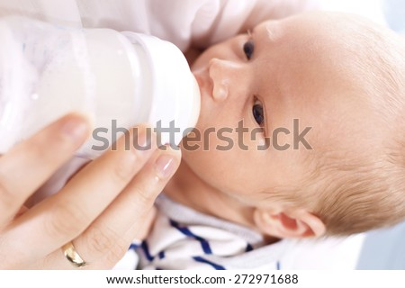 Infant nutrition. A woman feeds a newborn with modified milk from a bottle  - stock photo