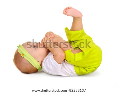 infant on a white background.child bites the leg.girl is a baby