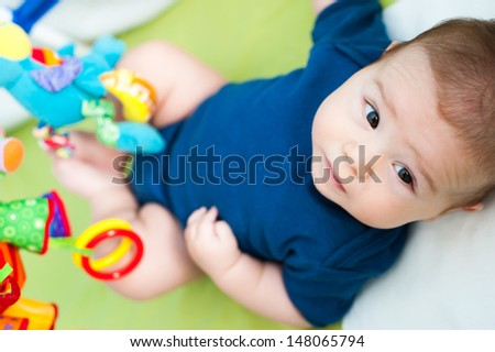 Infant playing in his crib - stock photo