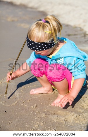 Infant preschool girl playing on a beach - stock photo
