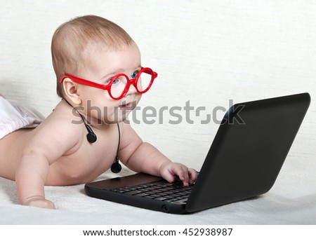 Infant red glasses with headphones on his neck enthusiastically looking at the computer