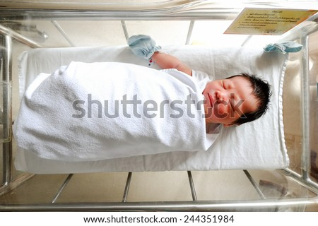 Infant sleeping in bowl at hospital with white blanket - stock photo