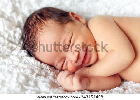 infant smiling in his sleep - stock photo