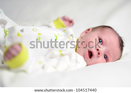 Infant with Open Mouth. Baby boy laying on a white blanket with an open mouth. Shallow DOF. - stock photo