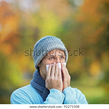 Infected man blowing his nose in tissue paper because of being ill or allergy - stock photo