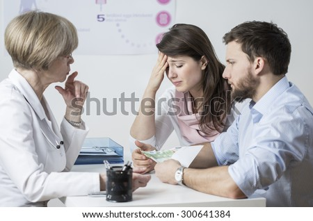 Infertile couple giving a bribe for IVF treatment - stock photo